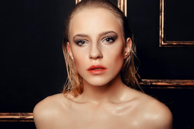 Uroda moda model dziewczyna naturalny makijaż mokre włosy na czarnym złotym tle w ciepłych kolorach. portret młodej kobiety z makijażem mody