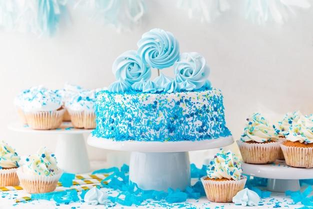 Urodzinowa batonika z niebieskim tortem, babeczkami i bezą.