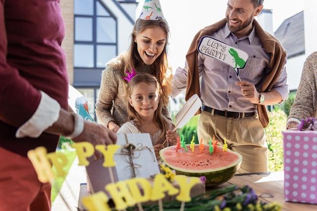Urodzinowa dziewczyna. urocza młoda kobieta trzyma uśmiech na twarzy, obejmując córkę