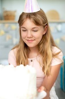Urodzinowa dziewczyna ze średnim strzałem trzyma tort