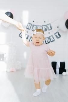 Urodzinowa dziewczynka 1 rok trzyma matkę za rękę i jest oburzona, nieszczęśliwa
