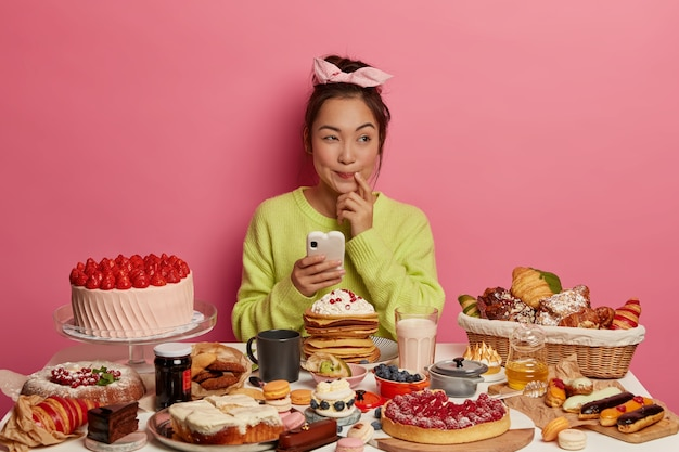 Urodzinowa kobieta myśli o zaproszeniu na przyjęcie wysyła wiadomości do przyjaciela przez telefon komórkowy piecze różne desery dla gości nie może się doczekać smacznego słodkiego jedzenia