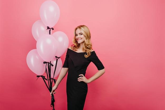 Urodzinowa ładna dziewczyna w eleganckie ubrania trzymając balony. kryty zdjęcie radosnej młodej kobiety z jasnymi włosami świętuje coś.
