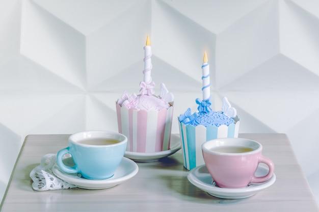 Urodzinowe babeczki z urodzinową świeczką i filiżankami herbaty