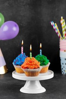 Urodzinowe babeczki z zapalonymi świeczkami