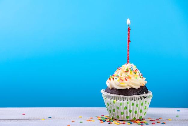 Urodzinowe ciastko na niebiesko z kolorowych świec.