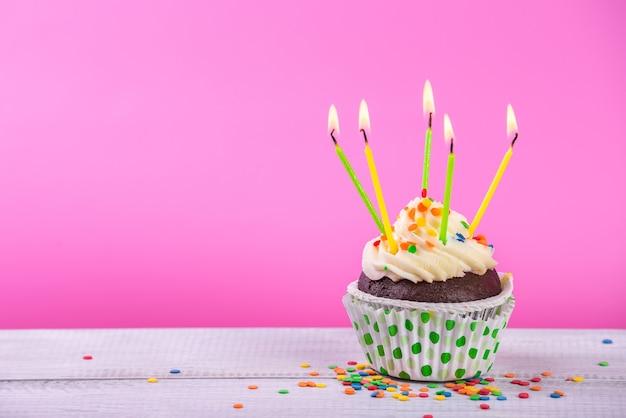 Urodzinowe ciastko na różowo z kolorowych świec.