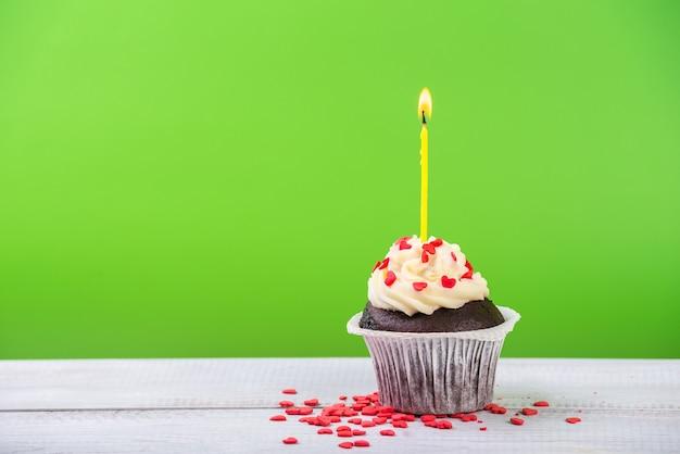 Urodzinowe ciastko na zielono z kolorowymi świecami.