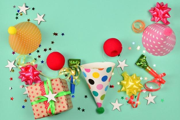 Urodzinowe czapki, prezent, konfetti, wstążki, gwiazdki, nosy klauna na zielonym tle. miejsce na tekst lub projekt.