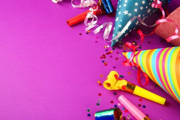 Urodzinowe czapki z serpentynową serpentynową serpentynami i fioletowymi znacznikami hałasu