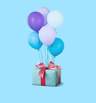 Urodzinowe pudełko z kolorowym balonem na pastelowym tle