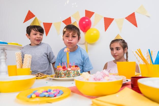 Urodzinowy chłopiec dmuchania świeczka z jego przyjaciółmi