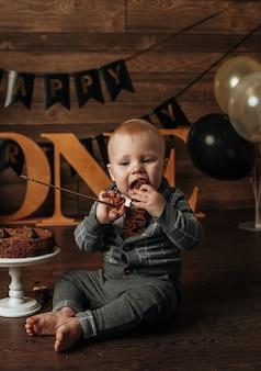 Urodzinowy chłopiec w szarym garniturze zjada ciasto czekoladowe na brązowym tle