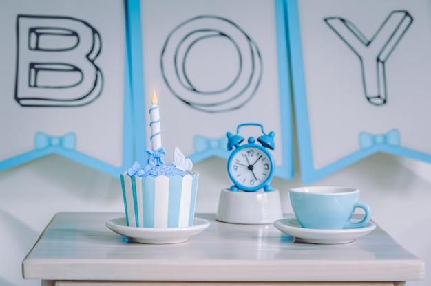 Urodzinowy deser babeczki z niebieskim budzikiem i filiżanką herbaty.