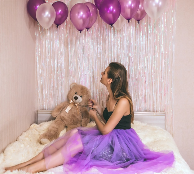 Urodzinowy dziewczyny zbliżenie w purpury spódnicie. młoda ładna kobieta siedzi na łóżku z fioletowymi kulkami w dłoni