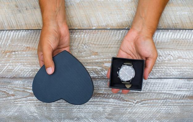 Urodzinowy pojęcie na drewnianym tła mieszkaniu nieatutowym. mężczyzna trzyma pudełka z zegarkiem.