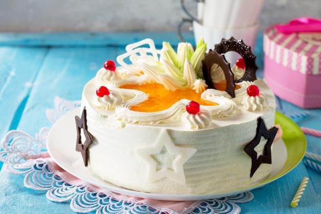 Urodzinowy tort biszkoptowy z bitą śmietaną z kolorowymi świeczkami na niebieskim tle
