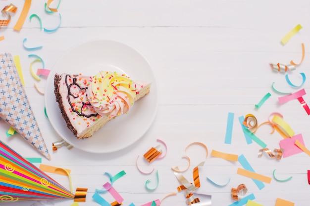 Urodzinowy tort i confetti na białym drewnianym tle