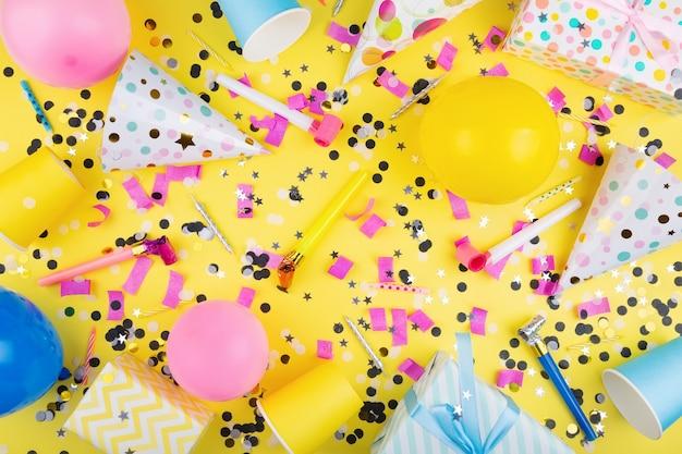 Urodziny atrybuty kolorowe kulki konfetti prezenty papierowe kubki czapka imprezowa