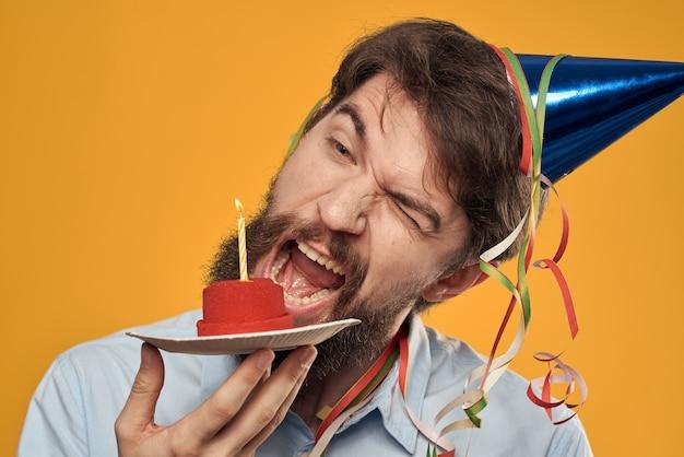 Urodziny chłopca w czapce z tortem urodzinowym w ręku i świeczką