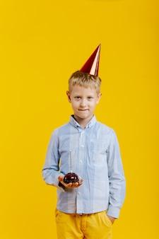 Urodziny chłopca z kapeluszem strony, trzymając muffinkę
