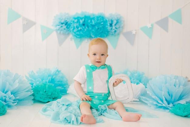 Urodziny chłopiec roczny chłopiec, opiekunka z niebieskimi girlandami i literą o w garniturze i muszce