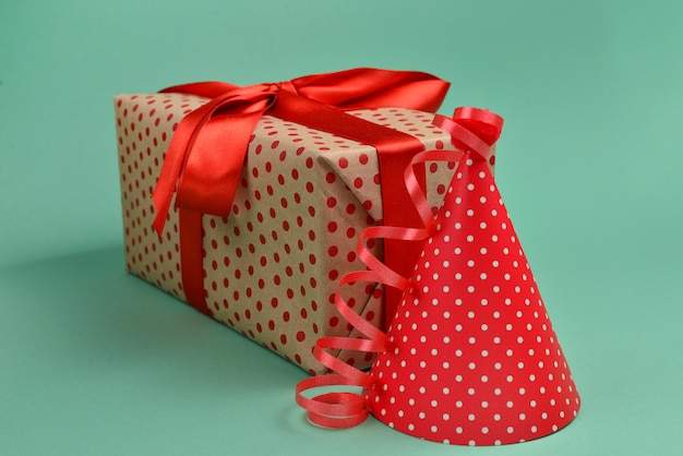 Urodziny czerwona czapka i prezent na zielonym tle. miejsce na tekst lub projekt.