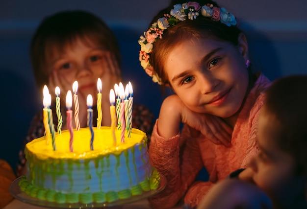 Urodziny dzieci dzieci w pobliżu tort urodzinowy ze świecami.