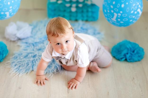 Urodziny dziecka chłopiec 1-letni, widok z góry, dziecko pełzające wśród balonów w garniturze i muszce