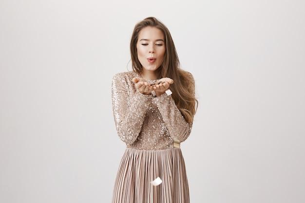 Urodziny dziewczyna w wieczorowej sukni dmuchanie confetty z dłoni