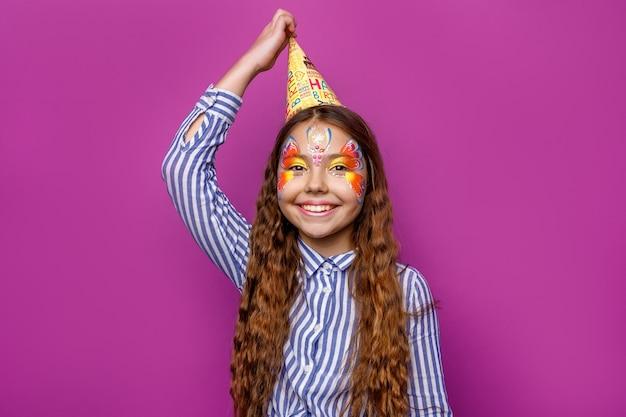 Urodziny dziewczyna z kolorowym faceart nosić czapkę party pozowanie na białym tle na fioletowej ścianie.