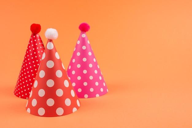 Urodziny kolorowe czapki na pomarańczowym tle. widok z góry.