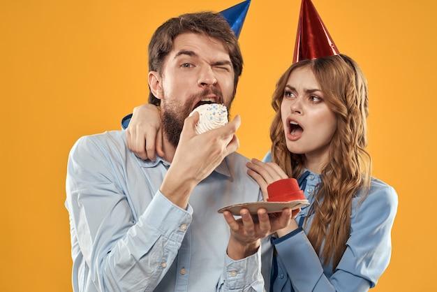 Urodziny, mężczyzna i kobieta, zabawa, żółte tło, czapka, wakacje