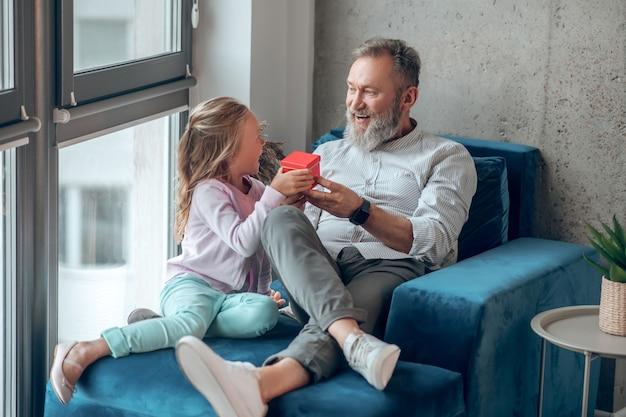 Urodziny ojców. słodka blondynka daje prezent ojcu