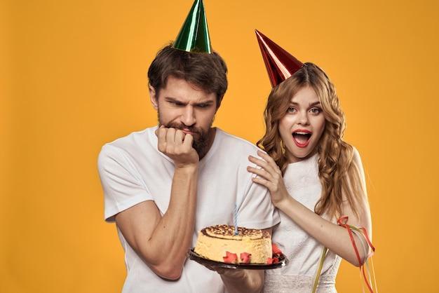 Urodziny para z tortem i świeczką na sobie czapki na białym tle
