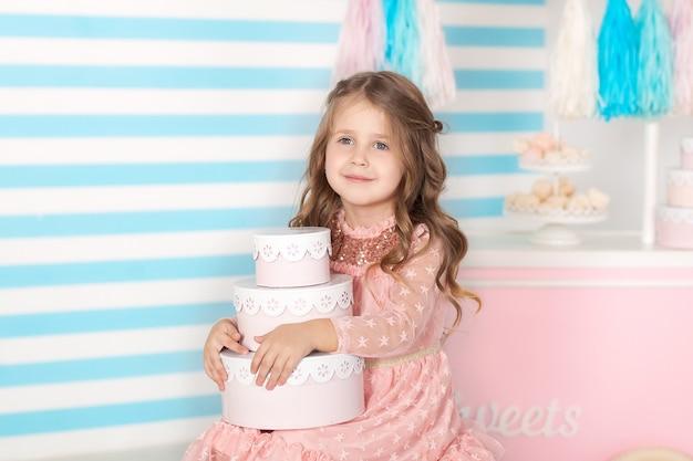Urodziny! piękny małej dziewczynki obsiadanie z prezentami. pasek urodzinowy candy. portret dziecka twarzy zbliżenie.