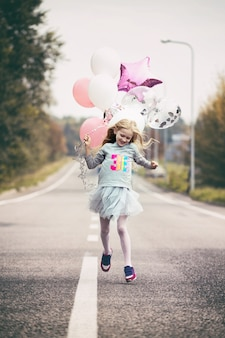 Urodziny - szczęśliwa dziewczyna z balonami biegną wzdłuż rozdzielającego pasa drogi