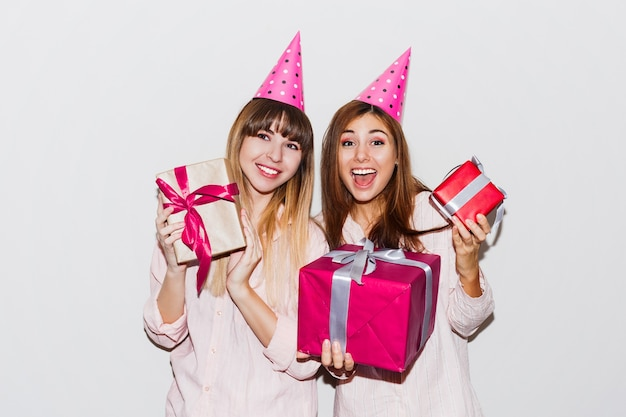 Urodziny w piżamie. przyjaciele, zabawy i trzymając pudełka. zaskoczona buźka, ekscytujące emocje dziewczyny w czapkach z rekwizytami.