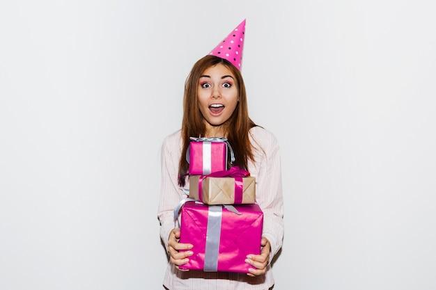Urodziny w piżamie. śliczna dziewczyna z twarzą niespodzianką, trzymając pudełka na prezenty, ubrana w rekwizyty czapki. portret z lampą błyskową.