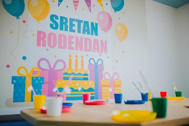 Urodziny w przedszkolu z kolorową zastawą stołową na drewnianych małych stolikach