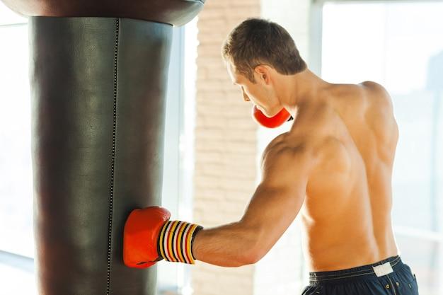 Urodzony by walczyć. pewny siebie młody bokser w rękawicach sportowych trenujących na siłowni
