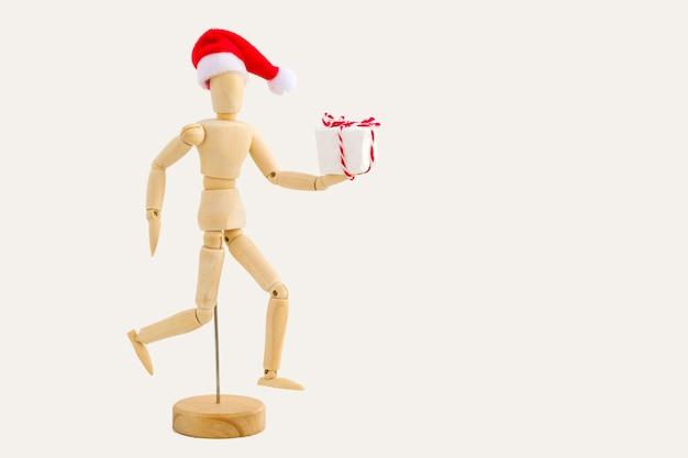 Uruchamiana drewniana figura - manekin artystyczny z czerwoną czapką mikołaja z pudełkiem. koncepcja biznesowa i projektowa na boże narodzenie