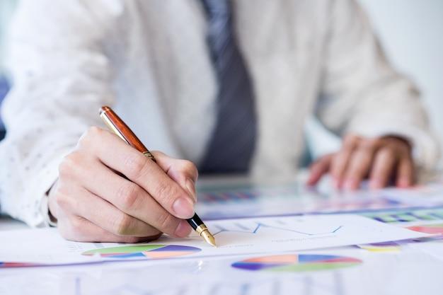 Uruchamianie procesu roboczego. biznesmen pracy na stół drewna z nowym projektu finansów. nowoczesny notebook na stole. dłoń trzymająca pióro