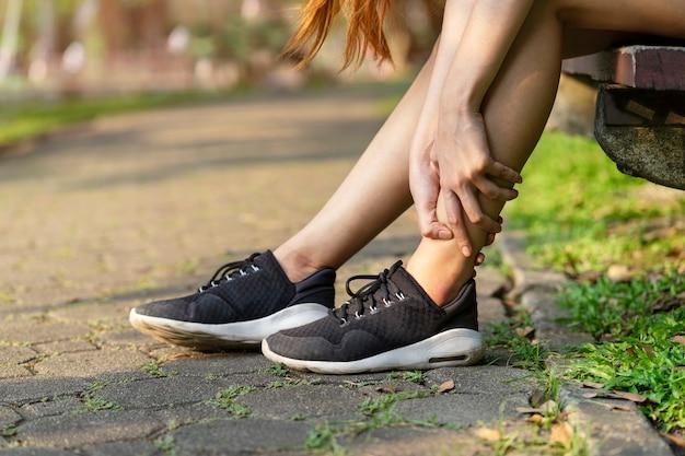 Uruchamianie wypadku nogi nogi. sport kobieta biegacz dotykając bolesne skręconą kostkę w bólu