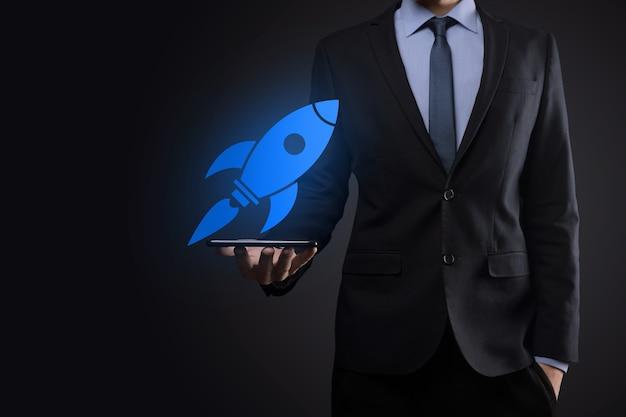 Uruchom koncepcję z biznesmenem posiadającym abstrakcyjną cyfrową rakietę z ikoną rakiety, która wystrzeliwuje i szybuje w powietrzu