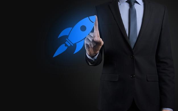 Uruchom koncepcję z biznesmenem posiadającym abstrakcyjną cyfrową rakietę z ikoną rakiety, która wystrzeliwuje szybować