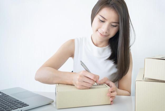 Uruchom małe przedsiębiorstwo przedsiębiorczości mśp lub niezależną kobietę piszącą na kartonie pracującym w domu