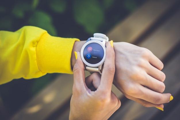 Uruchom ponownie lub zamknij. zbliżenie na smartwatch na dłoni dziewczyny, proszący o ponowne uruchomienie lub wyłączenie, z dwoma palcami dziewczyny z żółtymi paznokciami klikającymi przyciski.