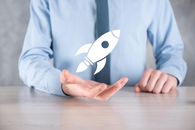 Uruchomić koncepcję z biznesmenem posiadającym abstrakcyjną cyfrową ikonę rakiety rakieta uruchamia się i szybuje w powietrzu.