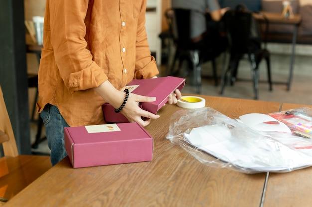 Uruchomienie małej firmy kobieta właściciela opakowania karton w miejscu pracy.